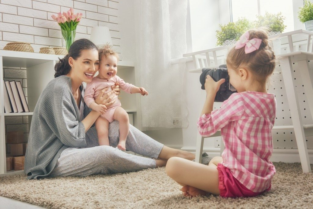 Girl taking a photo of her mom and sister