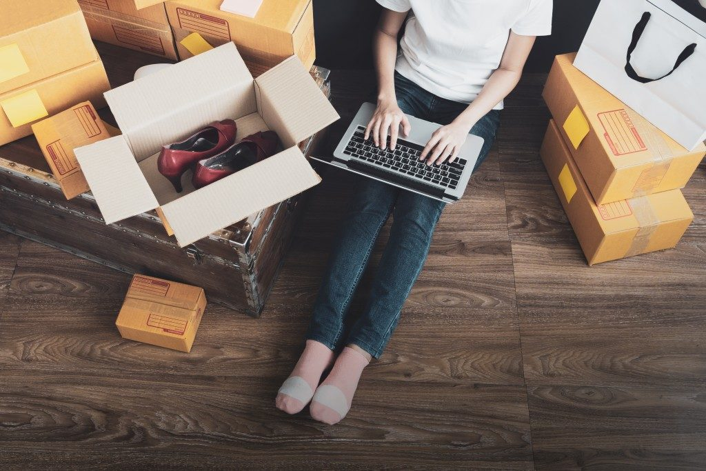 online store owner with a laptop surrounded by shipment boxes